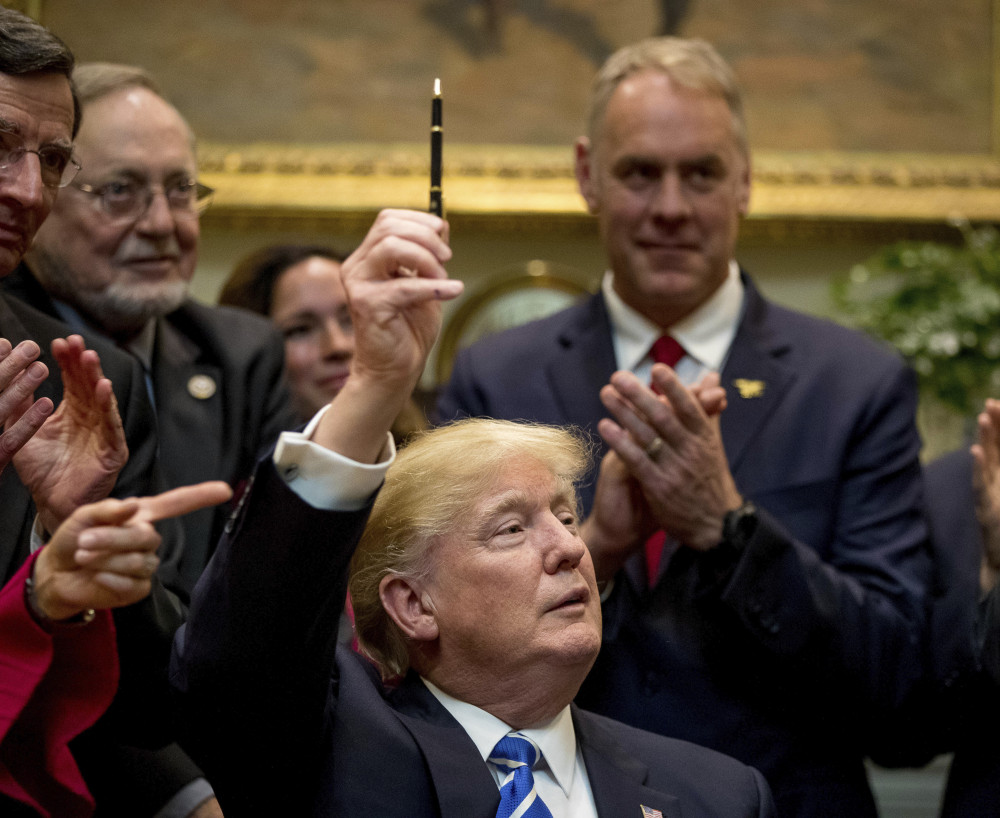 President Trump holds up the pen he used to sign a bill in the Roosevelt Room of the White House on Monday. From left are Sen. Tom Barrasso, R-Wyo., Rep. Don Young, R-Alaska, and Interior Secretary Ryan Zinke.