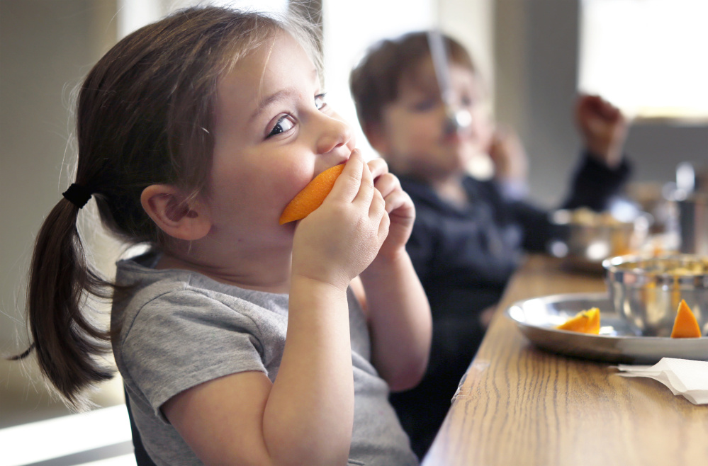Camille Pitzer, 3, bites into a freshly sliced orange at MaineLy Childcare in South Portland.