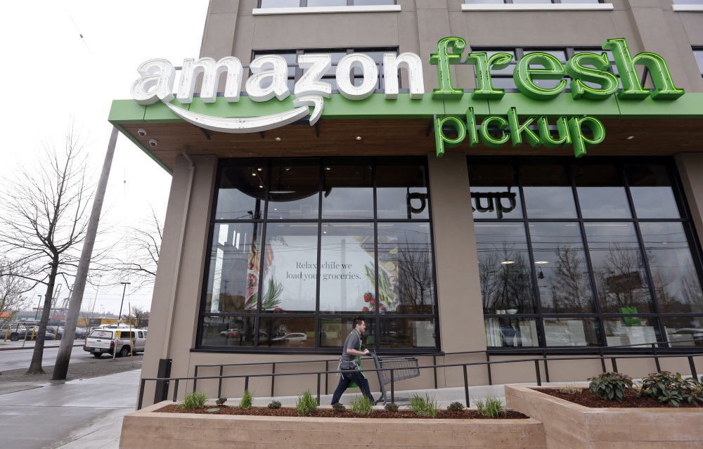 A worker returns a cart after loading groceries ordered online into a customer's car at an AmazonFresh Pickup location Tuesday in Seattle. Amazon is currently beta testing the free service with employees.