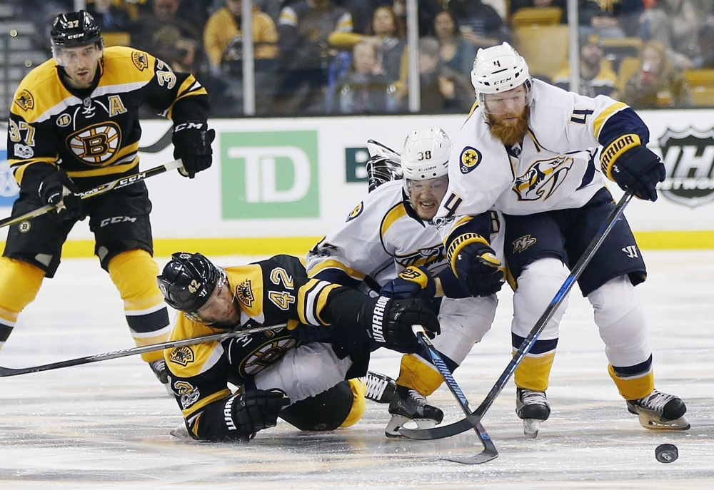 Boston's David Backes, 42, battles Nashville's Viktor Arvidsson, center, and Ryan Ellis for the puck during the second period of the Bruins' 4-1 win Tuesday in Boston.