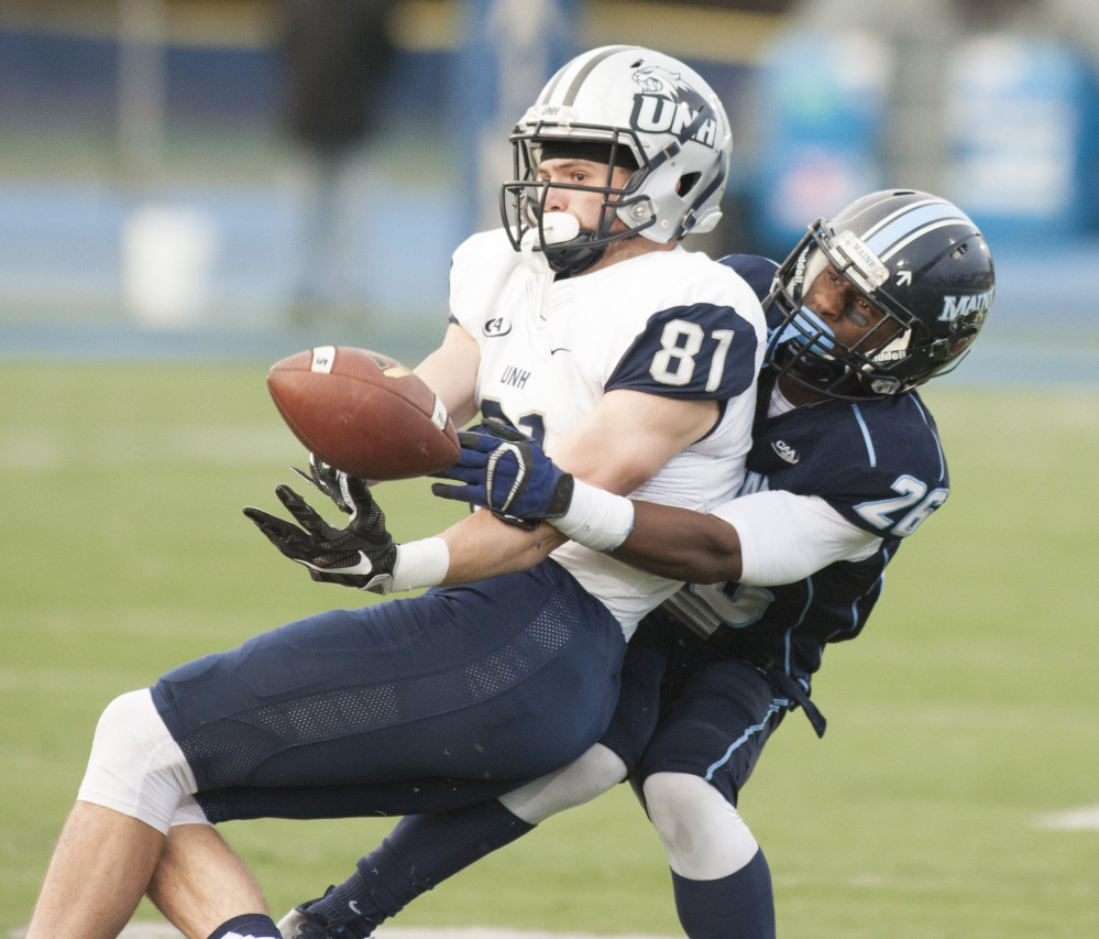UMaine's Manny Patterson, right, grapples for the ball as he brings New Hampshire receiver Rory Donovan to the ground on Nov. 19 in Orono. UNH won the game, 24-21. (Kevin Bennett photo)