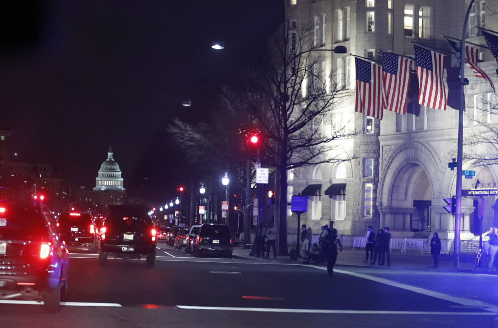 The president's motorcade arrives at the Trump International Hotel, right, where he had dinner Saturday night. The Trump Organization is scouting for a new hotel site in Washington.