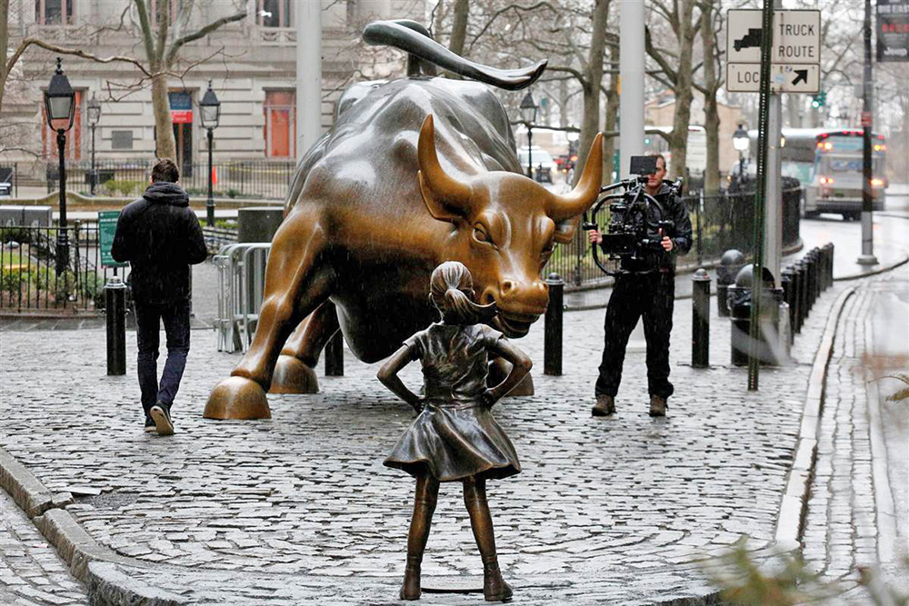 A camera man films the statue of a girl facing the Wall St. Bull in the New York financial district.