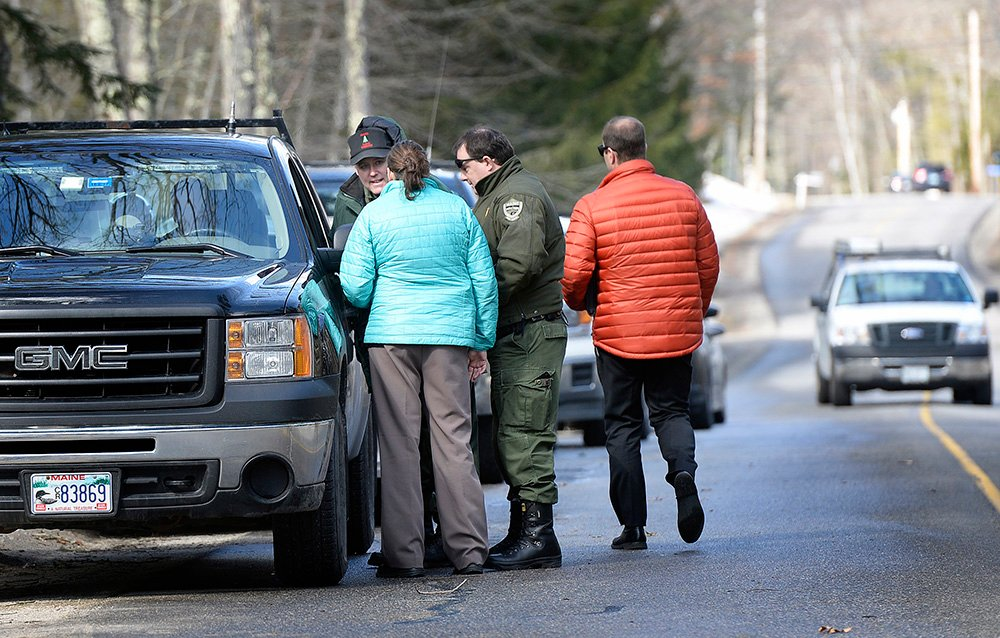 Detectives and game wardens talk Thursday at the scene in Arundel where Maine State Police are investigating the death of 63-year-old Matthew Coito, which they characterized as suspicious.