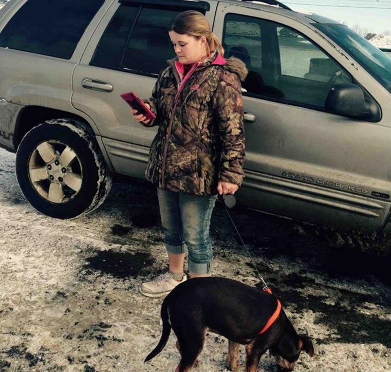 Nicole Bizier, 32, stands by her silver Jeep in the Pizza Hut parking lot with the puppy she tried to sell to state animal welfare agents and Skowhegan police on Feb. 2.