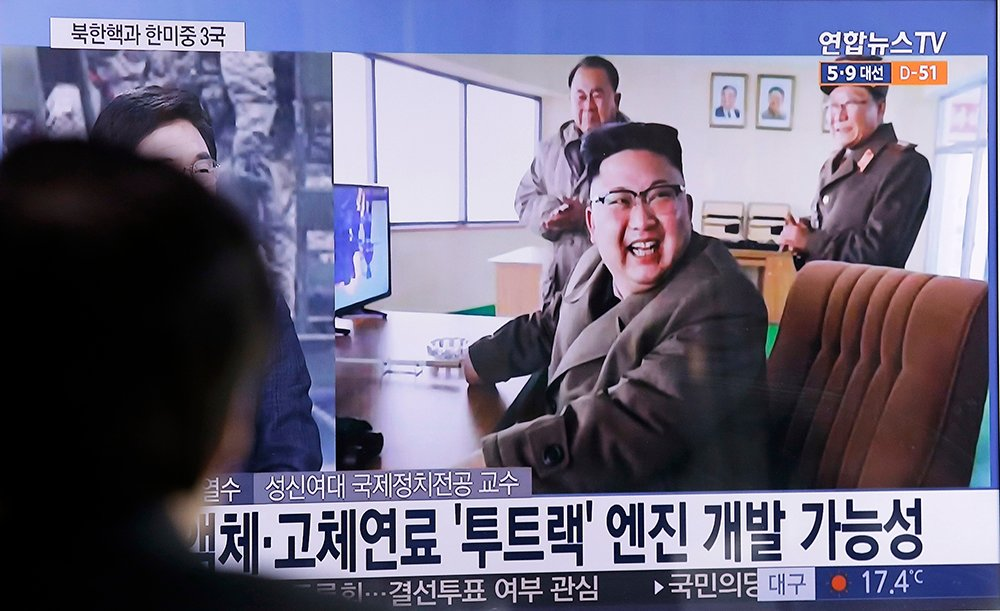 A man at a Seoul railway station watches a TV news program Sunday showing an image, published in North Korea's Rodong Sinmun newspaper, of North Korean leader Kim Jong Un at the country's Sohae launch site.