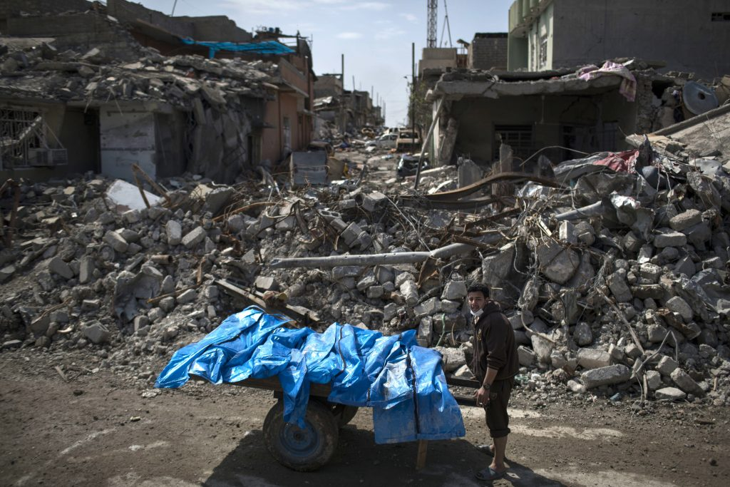 A resident carries the bodies of six people killed during fights between Iraq security forces and the Islamic State on the western side of Mosul, Iraq, on Friday.