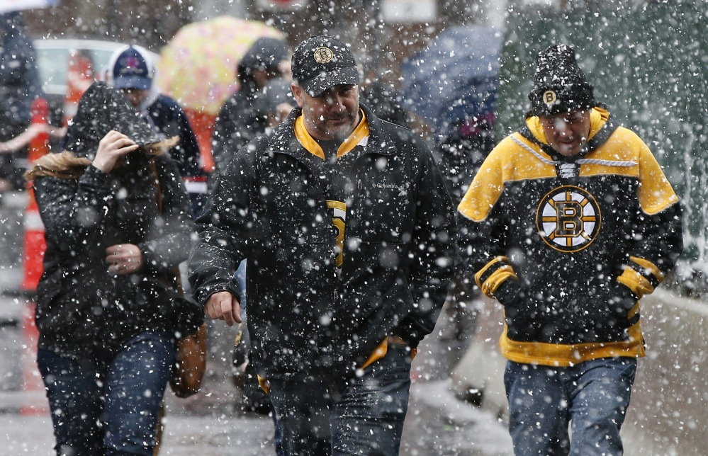 Boston Bruins fans walk to the game against the Florida Panthers at TD Garden as snow falls Saturday in Boston. The fans who braved the April Fool's storm were rewarded with a 5-2 Bruins win. (Associated Press/Michael Dwyer)
