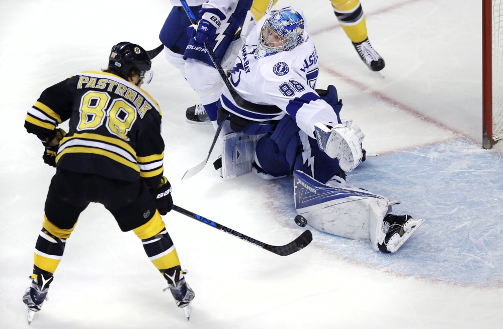 Tampa Bay Lightning goalie Andrei Vasilevskiy, right, makes a save on a shot by Boston Bruins right wing David Pastrnak during the Bruins' 4-0 win Tuesday in Boston.
