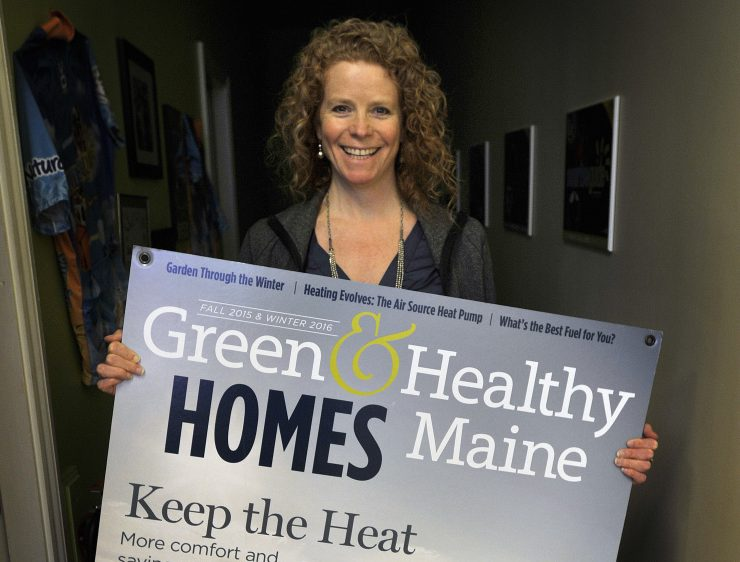 Heather Chandler, founder of the Sunrise Guide, shows off a poster of the cover of Green & Healthy Maine Homes, a magazine that she publishes.