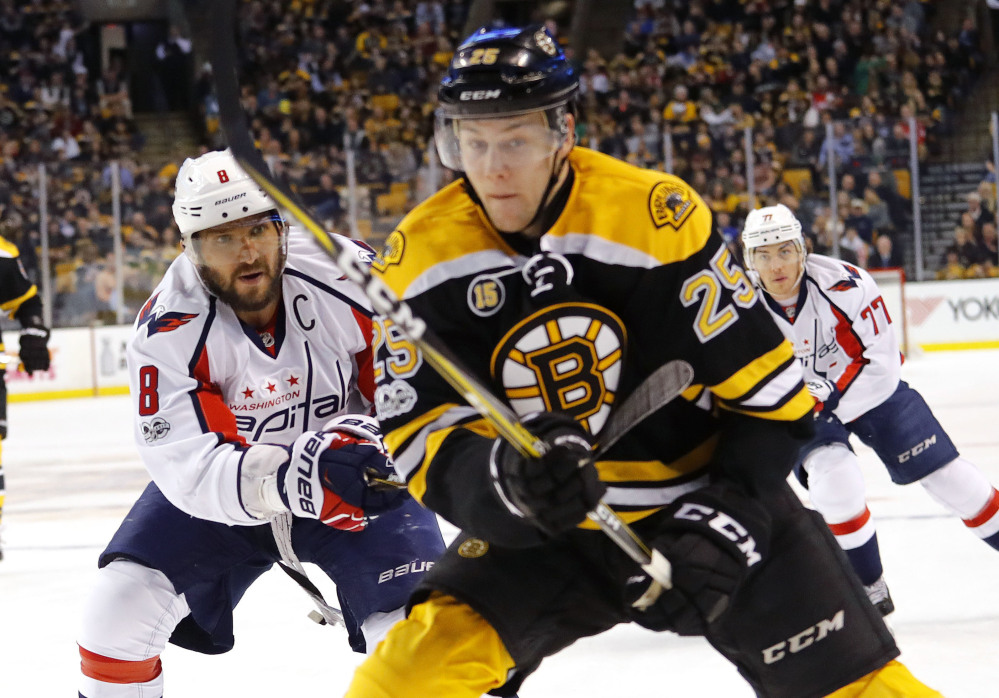 Alex Ovechkin of the Capitals moves in to check Bruins defenseman Brandon Carlo into the boards in the first period Saturday at TD Garden. Carlo was injured and did not return, and the Bruins lost, 3-1.