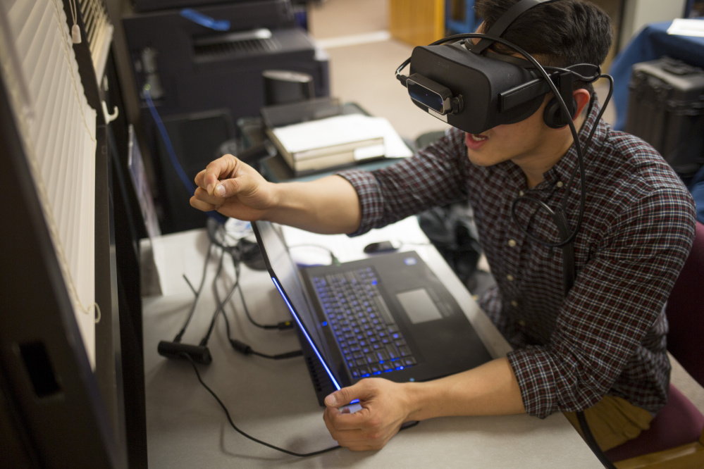 Ryan Hoang, a first-year medical student at UNE, experiences how just grasping a pencil can be challenging when you're suffering from macular degeneration, courtesy of virtual reality software.