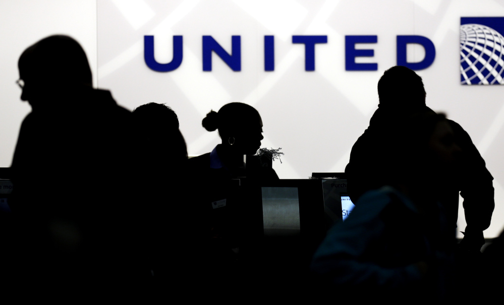 Travelers check in at the United Airlines ticket counter at O'Hare International Airport in Chicago, where a passenger who refused to give up his seat because of overbooking was dragged off the plane by police Sunday.