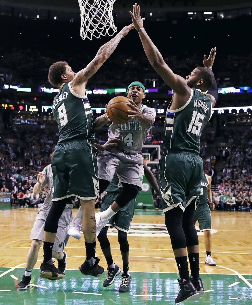 Celtics guard Isaiah Thomas, 4, threads between Bucks guard Matthew Dellavedova, 8, and center Greg Monroe on a drive to the basket during the first quarter Wednesday night in Boston.