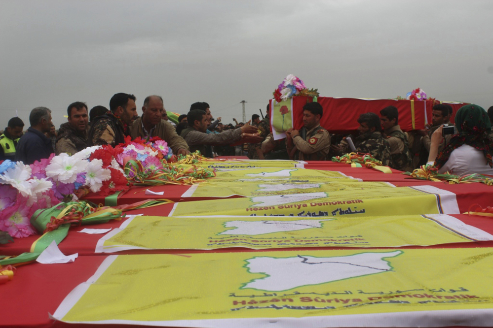 This photo provided by Hawar News Agency, a Kurdish-run news agency, which has been authenticated based on its contents and other Associated Press reporting, shows fighters from the predominantly-Kurdish Syrian Democratic Forces carrying the coffins of their comrades, who were killed Tuesday by a misdirected airstrike by the U.S.-led coalition, during their funeral procession, in Tal al-Abyad, northeast Syria, on Thursday.