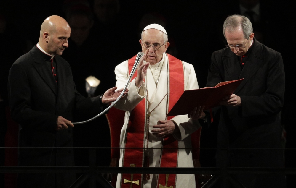 Pope Francis delivers his blessing as he presides over the Way of the Cross torchlight procession on Good Friday in front of Rome's Colosseum.