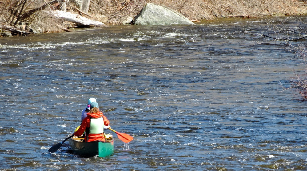 A duo celebrates the outdoors with a paddle on the whitewater below the Head Tide Dam.