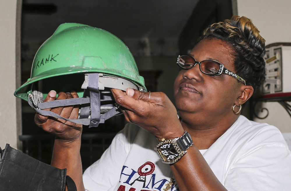Rochelle Hamm holds the hard hat of her late husband, Frank, at her home in Jacksonville, Fla. Associated Press/Gary McCullough