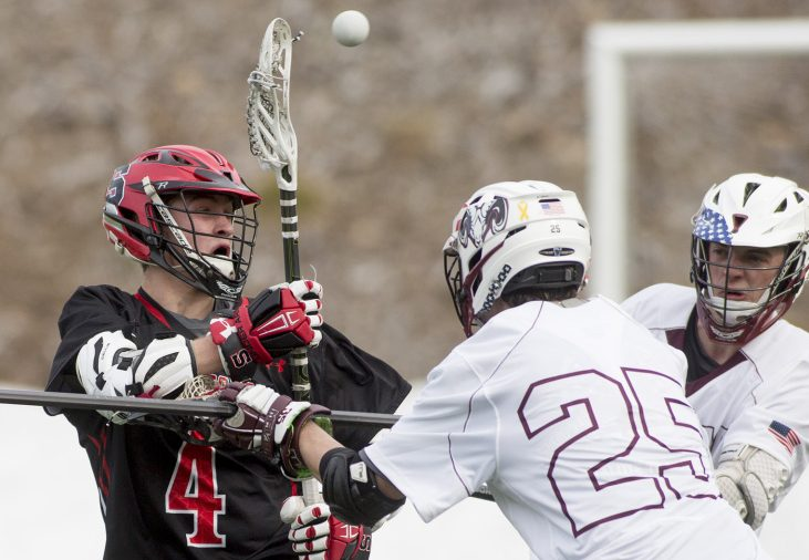 Scarborough's Marc Guerette passes the ball to a teammate as Mat Anderson, front, of Gorham defends during their boys' lacrosse season opener Saturday at the University of Southern Maine. Guerette was one of seven goal scorers for the Red Storm in a 15-9 victory.