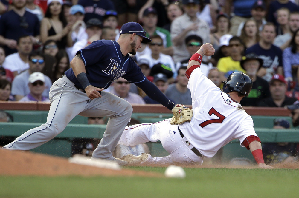 Tampa Bay's Daniel Robertson tags out Boston's Christian Vazquez, who tried to advance to third on a fly ball in the eighth inning Sunday at Fenway Park. Vazquez went 3 for 4 with an RBI double in Boston's 7-5 win.
