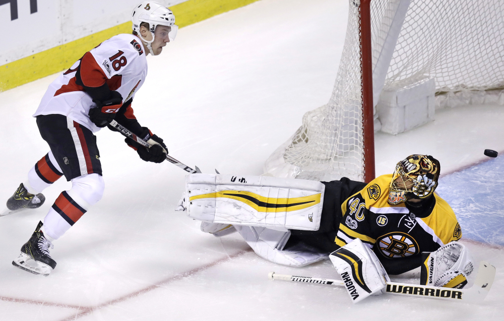 Bruins goalie Tuukka Rask (40) looks up at Ottawa Senators center Ryan Dzingel (18) as the puck flies through the crease during the first period.