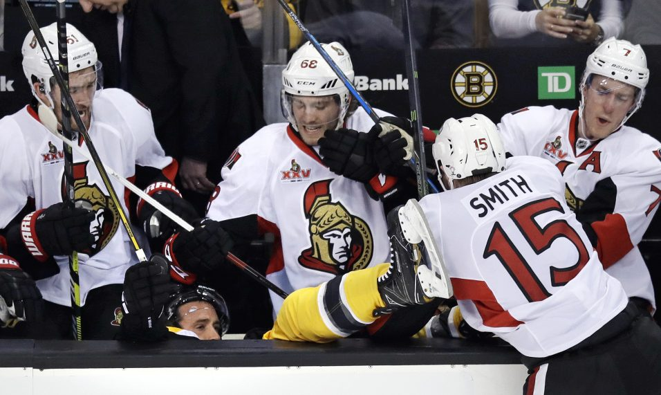 Ottawa Senators center Zack Smith (15) checks Boston Bruins center Ryan Spooner into the Senators bench during the third period in Game 3 of a first-round NHL hockey playoff series in Boston.