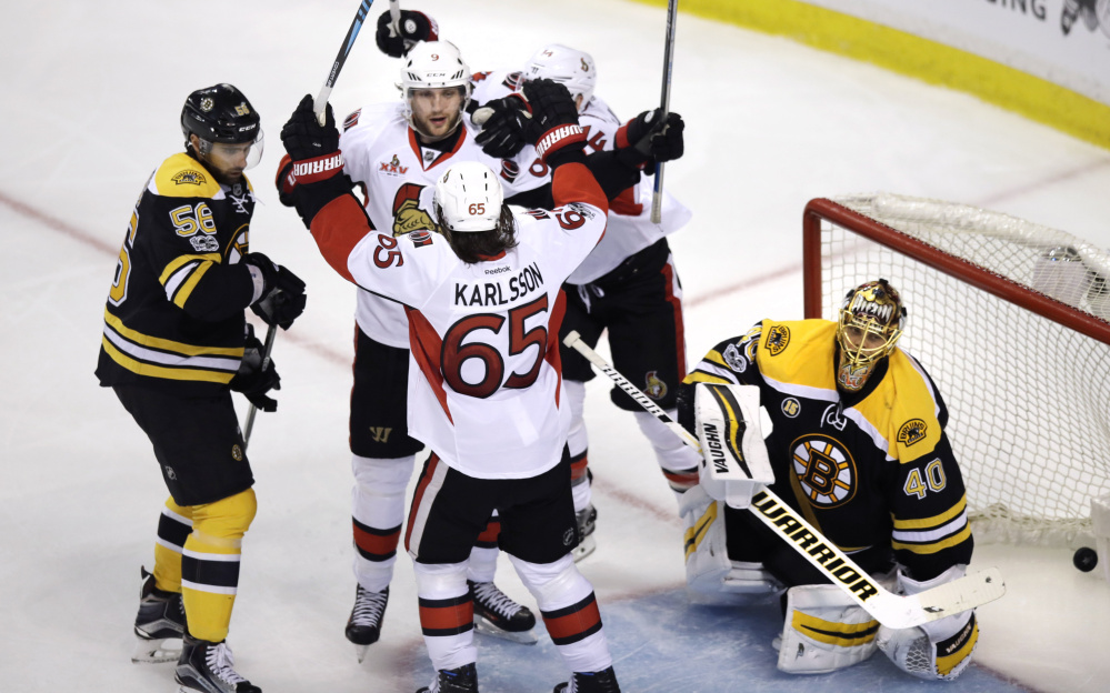 Bobby Ryan, facing front, celebrates with teammates after his OT goal Monday night in Boston. The Senators scored on the power play, the result of a controversial call on Riley Nash.