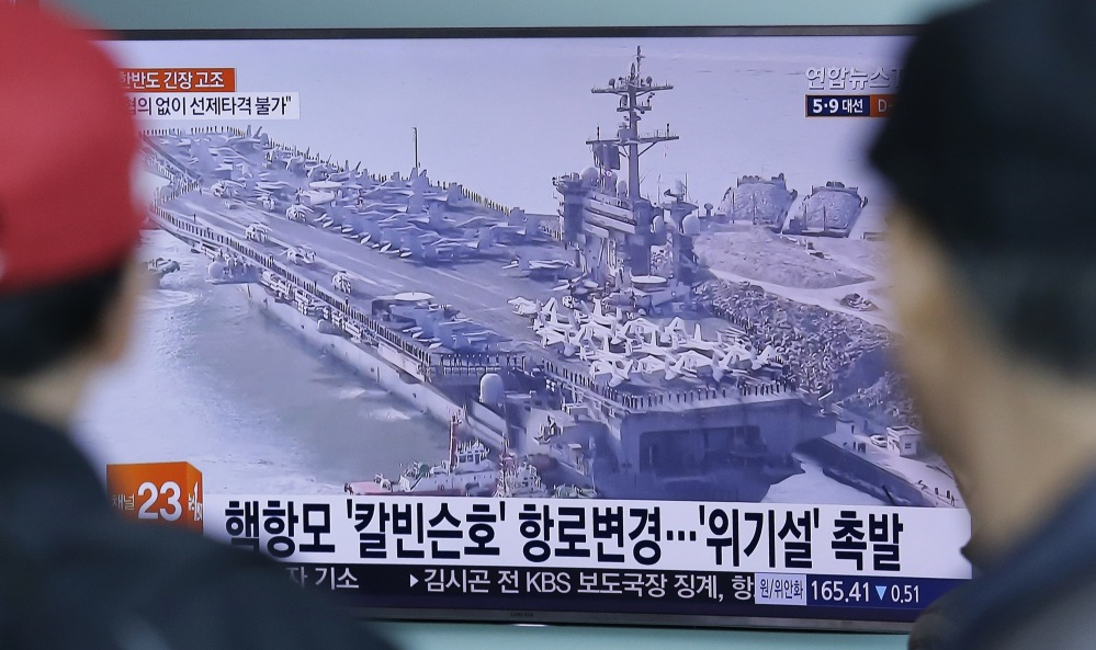 People in Seoul, South Korea, watch a TV news program showing a file image of the USS Carl Vinson aircraft carrier last week. The ship that U.S. officials portrayed as a sign of stepped-up response to North Korea was quietly operating in the Indian Ocean, thousands of miles away.