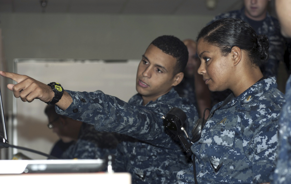 Petty Officer 3rd Class DonPaul Mitchell, left, assigned to the guided-missile submarine USS Georgia, instructs Ensign Tabitha Strobel, Georgia's main propulsion assistant, in a trainer at Naval Submarine Base Kings Bay in Georgia in 2012. With women now serving on submarines, future subs are being built to specifically accommodate gender differences including height, reach and strength.