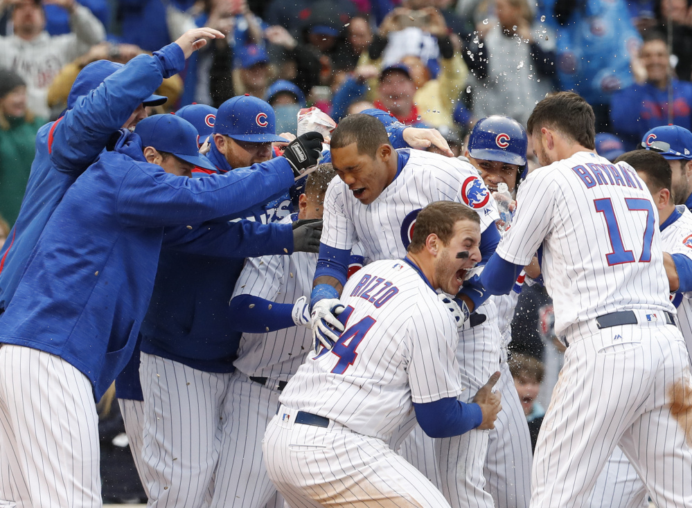 Addison Russell, center, of the Chicago Cubs celebrates with teammates after hitting a game-winning three-run homer in the ninth inning of a 7-4 win Wednesday in Chicago.