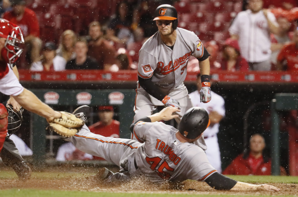 Mark Trumbo of the Baltimore Orioles avoids a tag by Cincinnati catcher Stuart Turner to score the go-ahead run Thursday night on a single by J.J. Hardy in the 10th inning. The Orioles, who will meet the Boston Red Sox this weekend, collected a 2-1 victory.