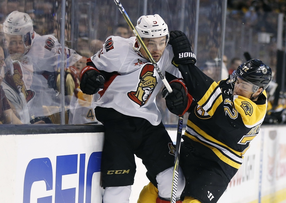 Boston's Frank Vatrano, right, checks Ottawa's Cody Ceci during the first period of the Senators' 3-2 overtime win in Game 6 of their first-round playoff series Sunday in Boston. Ottawa advanced, winning the series 4-2.