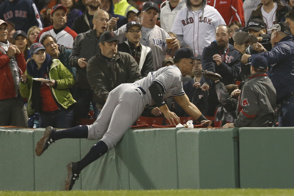 Aaron Judge of the Yankees dives into the stands to catch a foul ball hit by Boston's Xander Bogaerts in the third inning Wednesday night at Fenway Park.
