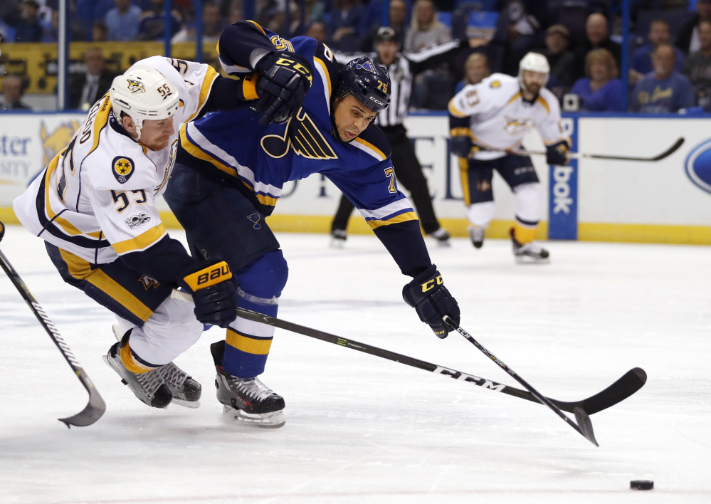 Ryan Reaves of the Blues, right, knocks Nashville's Cody McLeod off the puck in the first period Wednesday night in Game 1 of the Western Conference semifinals at St. Louis.