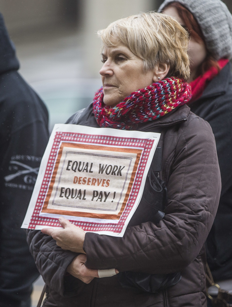 Kathy Liggett of Mishawaka, Ind., holds a sign during an Equal Pay Day rally on April 4 on the St. Joseph County Courthouse steps in South Bend, Ind.