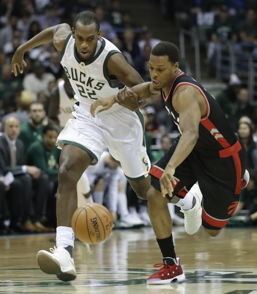 Khris Middleton, left of the Milwaukee Bucks and Kyle Lowry of the Toronto Raptors compete for a loose ball during the first half of Toronto's series-clinching victory Thursday night.