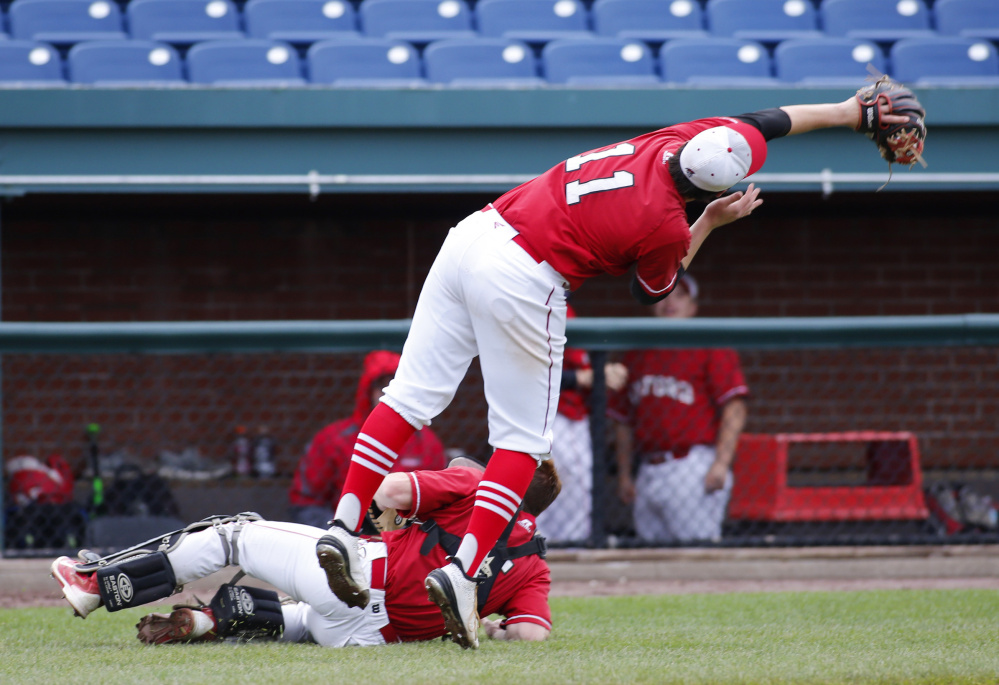 Sanford pitcher Frankie Veino reaches over catcher Nick Liston to make a play on an infield fly in the sixth inning.