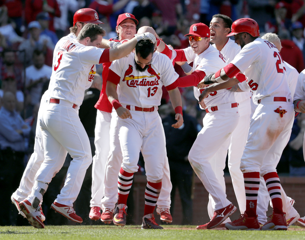 The Cardinals' Matt Carpenter is congratulated by teammates after his 11th-inning grand slam gave host St. Louis an 8-4 victory over the Blue Jays in the first game of a doubleheader on Thursday. The Cardinals won the night game, 6-4.