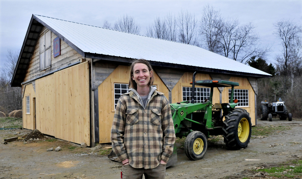 Farmer Johanna Davis stands in front of a barn Tuesday at her Songbird Farm in Unity. Songbird Farm is one of 10 in the country to receive a sustainability grant from The FruitGuys Community Fund. The farm received $2,966 to build a rainwater collection system. The system will help the farm conserve water, which will be an advantage in times of drought.