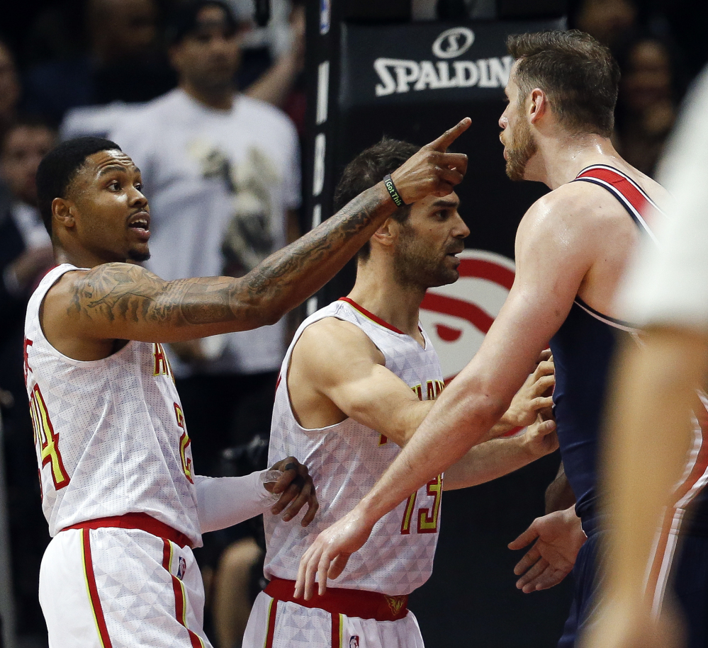 Kent Bazemore of the Atlanta Hawks, left, exchanges words with Jason Smith of the Washington Wizards during the first half of Washington's clinching victory.