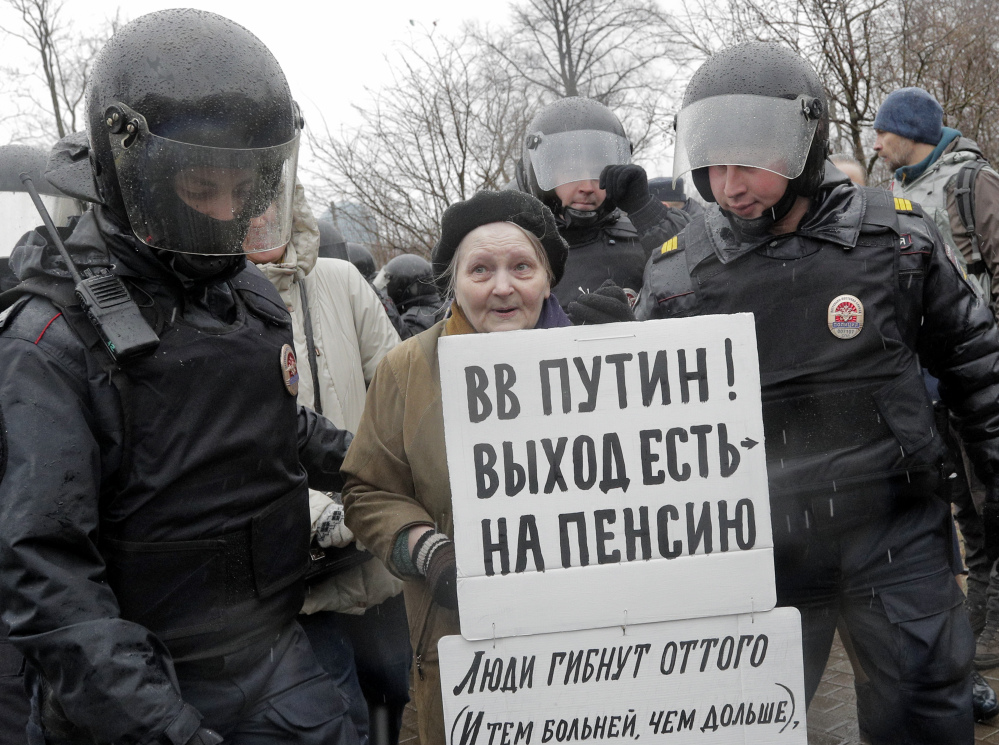 Police detain a participant of an unauthorized rally in St. Petersburg, Russia, on Saturday. A poster reads