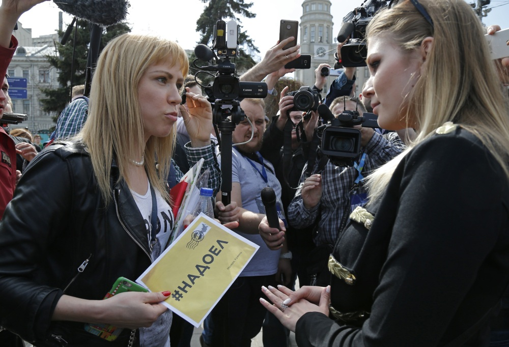 Opposition activist Maria Baronova, left, and pro-Kremlin political activist Maria Katasonova meet before an unsanctioned protest in downtown Moscow on Saturday. (Associated Press photos)