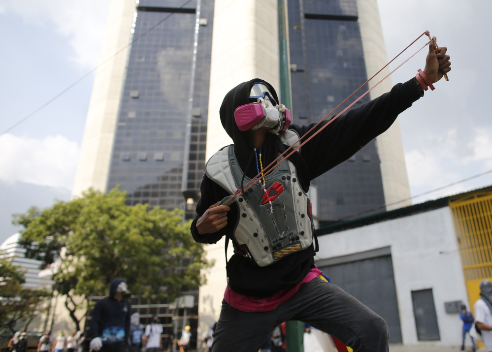An opponent of President Nicolas Maduro aims his slingshot as security forces block protesters from reaching the national ombudsman office in Caracas.
