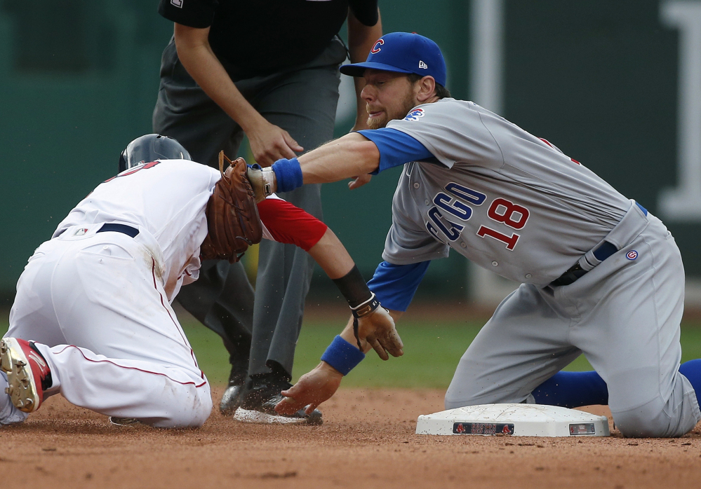 Chicago Cubs infielder Ben Zobrist  tags out Boston second baseman Dustin Pedroia, who was trying to reach on a single during the sixth inning Saturday.