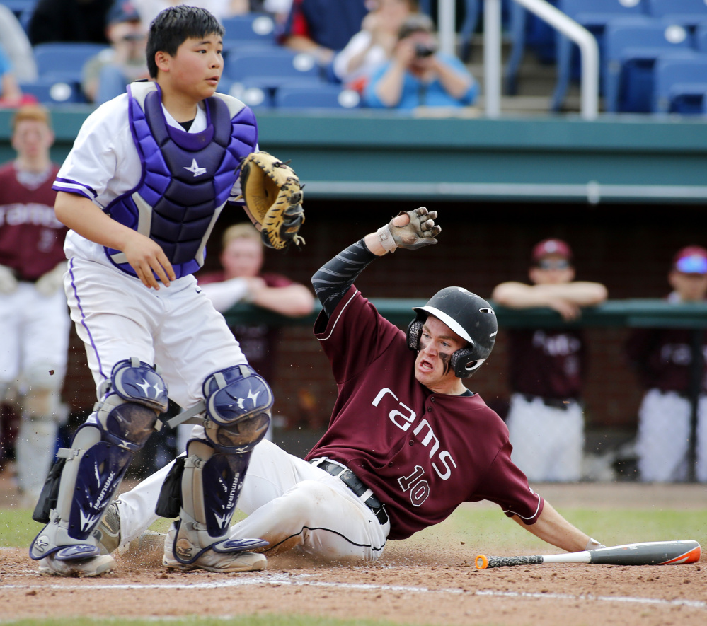 Nolan Brown of Gorham slides safely across the plate in the sixth inning as Deering catcher Princehoward Yee waits for the throw.