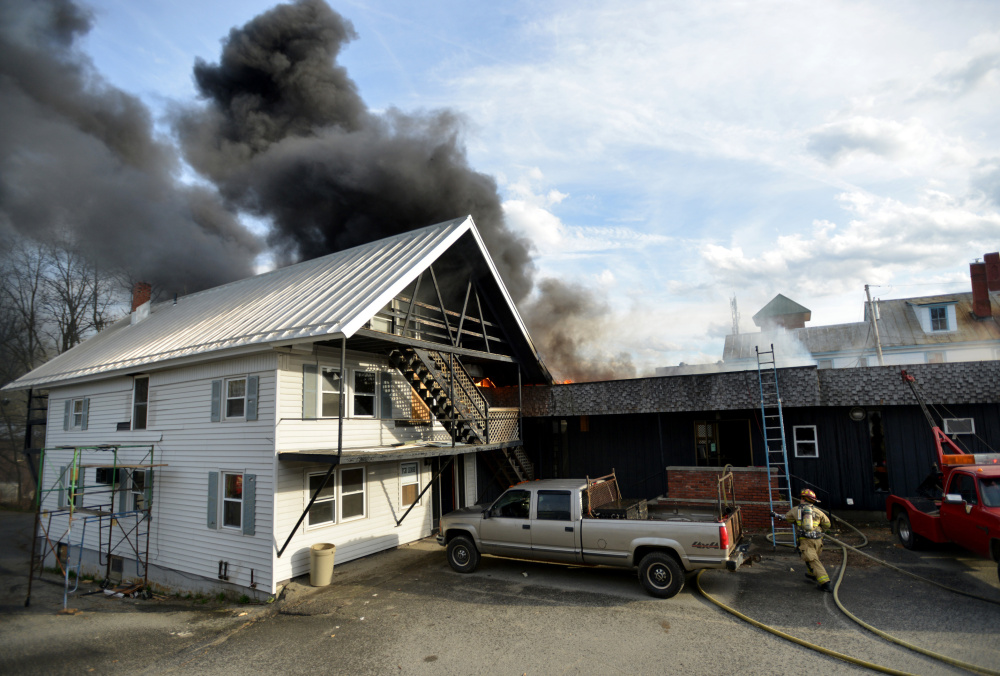 Firefighters battle a fire that spread to a second building on College Avenue in Waterville on Saturday.