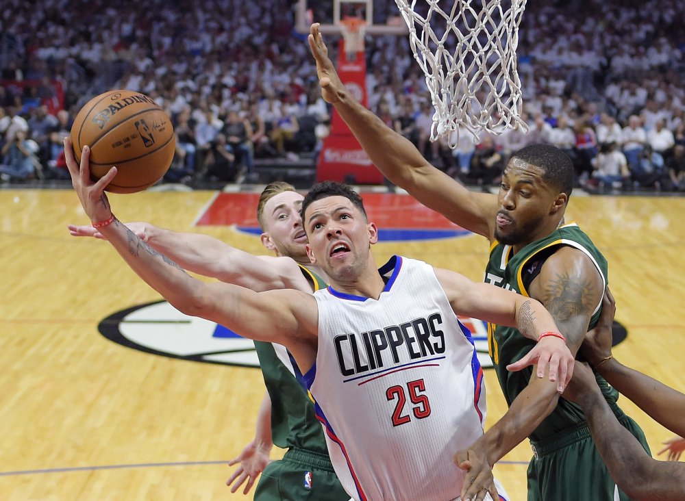 Los Angeles Clippers guard Austin Rivers, center, shoots as Utah Jazz forward Gordon Hayward, left, and forward Derrick Favors defend during the first half in Game 7 of an NBA basketball first-round playoff series, Sunday, April 30, 2017, in Los Angeles. (AP Photo/Mark J. Terrill)