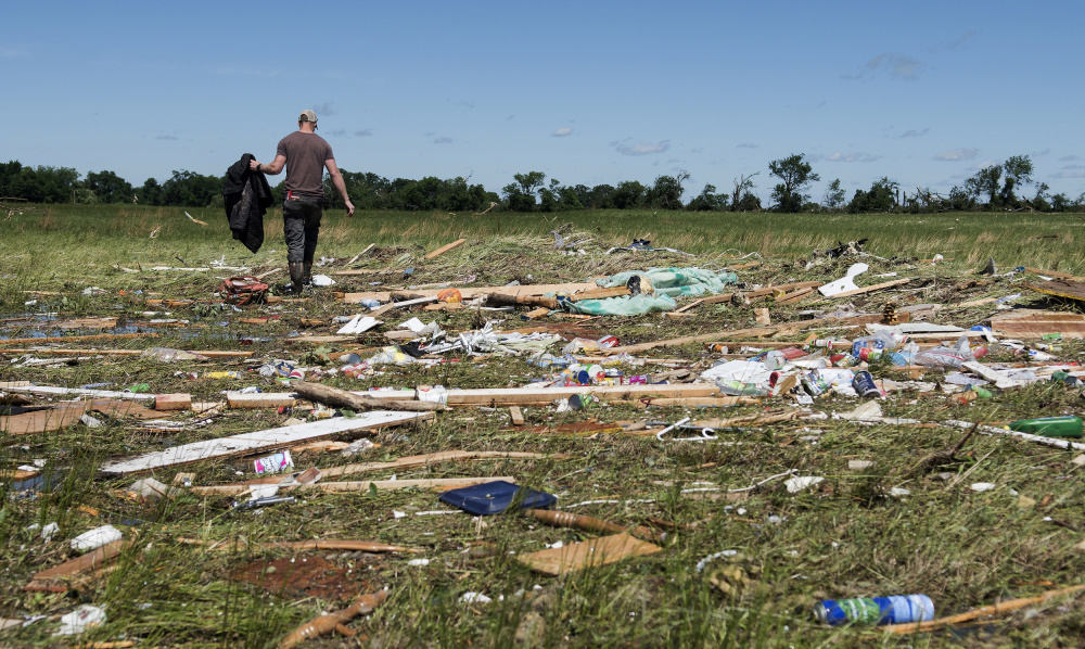 Kyle Allen walks his parents' property in Canton, Texas, on Sunday, looking for personal items. Severe storms, including tornadoes, swept through towns in East Texas on Sunday, killing several people, authorities said.