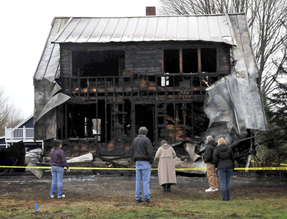 People survey the remains of this home on Main Street in Vassalboro Thursday morning that was destroyed by fire the previous night. The woman at far left is reportedly the owner.