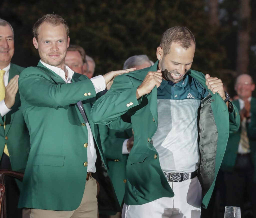 Danny Willett of England puts a green jacket on Sergio Garcia after the Masters on Sunday. It was Garcia's first major championship.